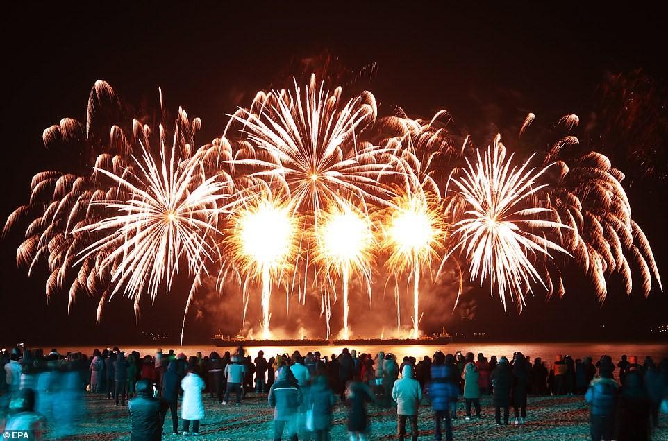 Người dân và khách du lịch theo dõi màn bắn pháo hoa đón chào năm mới tại bãi biển Yulpo
