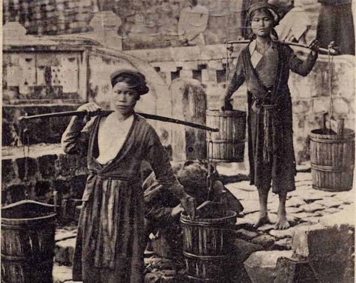 """Gánh nước: Khi những con phố ở thành thị, nhất là ở Hà Nội chưa có nước, người dân còn dùng nước giếng và nước ở máy nước công cộng. Nghề gánh nước thuê nhờ đó có đất sống. Nhất là vào dịp Tết, những người làm nghề gánh nước ăn nên làm ra vì gia chủ phải trả thêm cho họ để lấy may cho năm mới """"tiền vào như nước"""". Nguồn: Sách Nhiếp ảnh hiện thực và Việt Nam cuối thế kỷ 19 đầu thế kỷ 20."""