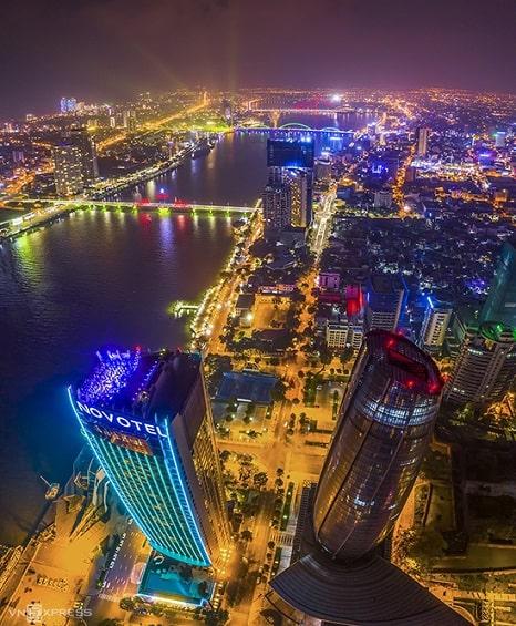 """Một góc thành phố Đà Nẵng rực rỡ sắc sắc màu về đêm. Được mệnh danh là """"thành phố đáng sống"""", nơi này có bờ biển đẹp, nhiều cao ốc, khu nghỉ dưỡng hiện đại. Mùa hè hàng năm, thành phố còn thu hút du khách bởi lễ hội pháo hoa quốc tế được tổ chức bên bờ sông Hàn."""