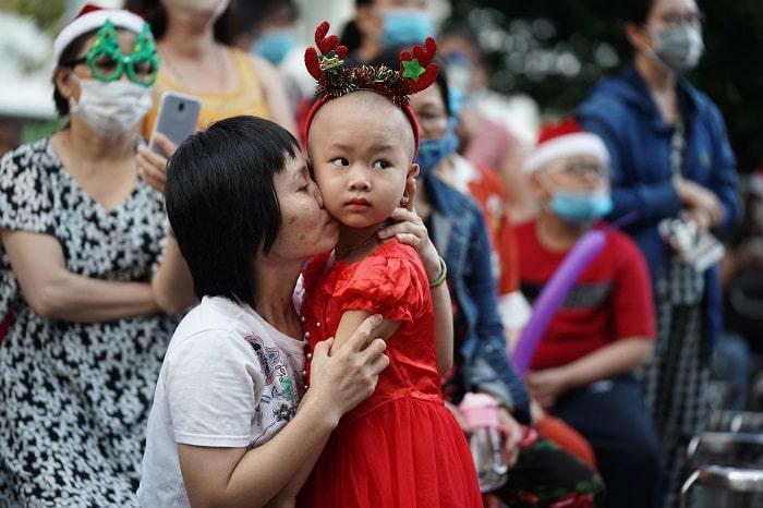 """Trẻ em đón Noel tại Bệnh viện Ung bướu, TP.HCM Chị Nguyễn Thị Mỹ Hoa (quê Bình Định) cho biết hơn nửa năm nay, con gái chị - bé Bảo Ngọc phát bệnh ung thư thận và phải cắt bỏ một quả thận. Ngọc đang được truyền hóa chất nên người luôn mệt mỏi. """"Tối nay, bé vui vẻ đòi mặc áo công chúa xuống chơi Noel cùng các bạn. Dù là năm đầu tiên cùng con đón Giáng sinh ở Bệnh viện Ung bướu TP.HCM, chúng tôi vẫn thấy ấm áp"""", chị Hoa chia sẻ. Tại bệnh viện này, một số người trong trang phục ông già Noel xuất hiện trao quà từ thiện cho nhiều bệnh nhân. Ảnh: Chí Hùng."""