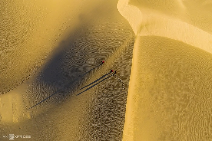 """Đồi cát Nam Cương thuộc địa phận xã An Hải, huyện Ninh Phước, tỉnh Ninh Thuận hiện lên như vùng sa mạc qua góc nhìn từ trên cao. Điểm đến này cách thành phố Phan Rang khoảng 8 km về phía đông nam. Tác giả cho biết, thời gian đẹp nhất để chụp ảnh đồi cát là sáng sớm và cuối giờ chiều. """"Khi bình minh lên, tia nắng len lỏi trên những trảng cát làm nổi bật lên các hình khối. Khi chiều đến (ảnh), sự thay đổi hình dạng liên tục của đồi cát tạo nên những đường nét tựa như dải lụa trong nắng vàng"""", Thảo chia sẻ."""