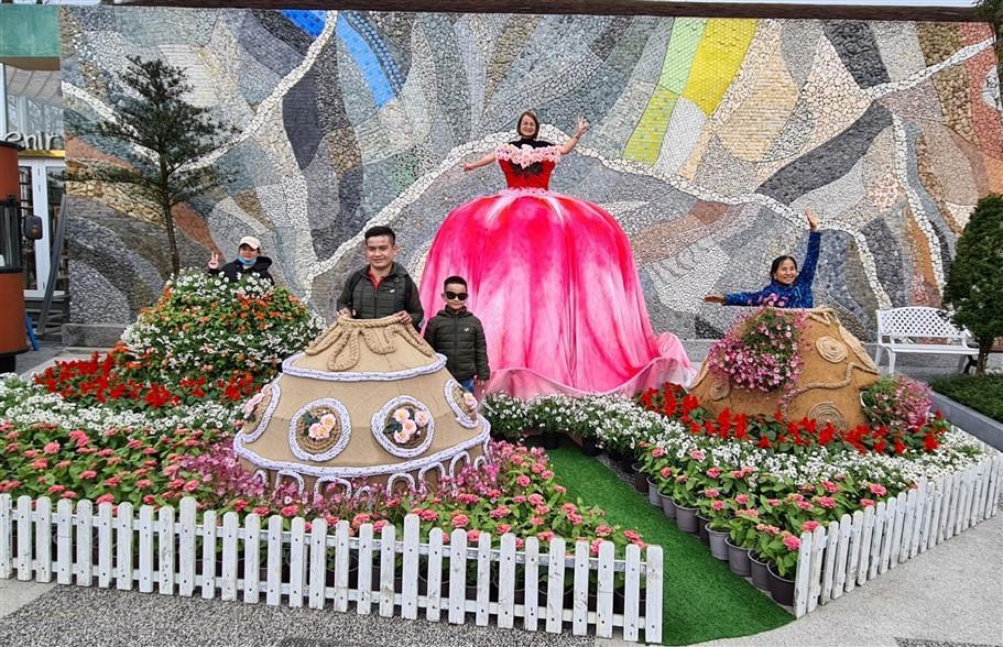 """Bước tới Vườn Uyên ương, du khách thỏa sức chiêm ngưỡng và """"thử dáng"""" với năm khung váy khổng lồ được kết từ những giỏ hoa tươi đủ loại."""